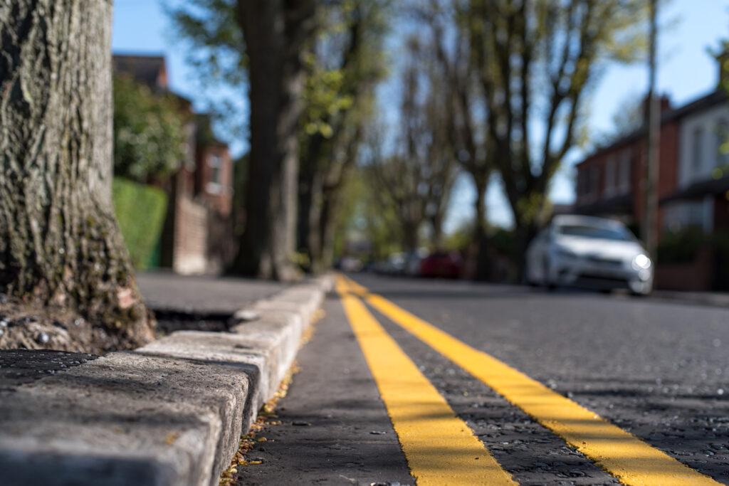 Close up de doubles lignes jaunes (ce qui signifie, pas de parking à tout moment) au bord d'une rue urbaine résidentielle bordée d'arbres, Belfast, Irlande du Nord.