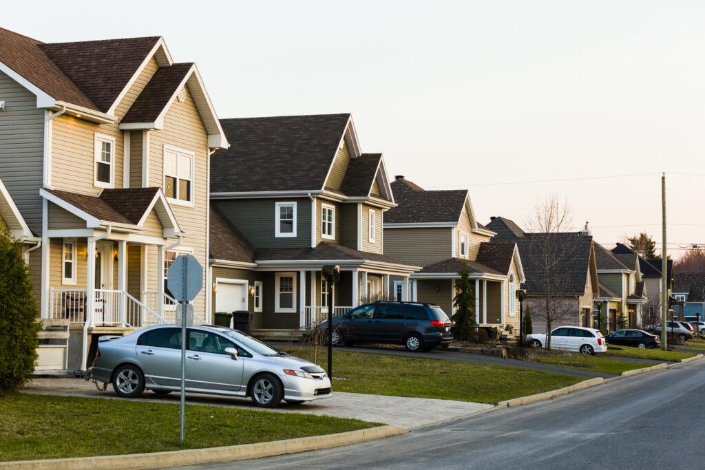 Ligne de maisons de banlieue chacune avec une voiture garée dans l'allée
